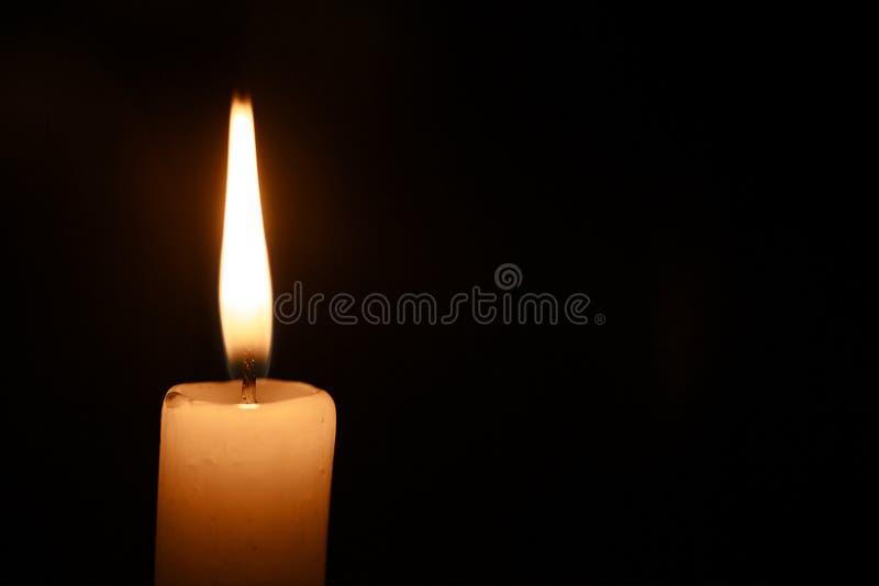 Una candela bruciante su fondo scuro immagine stock libera da diritti
