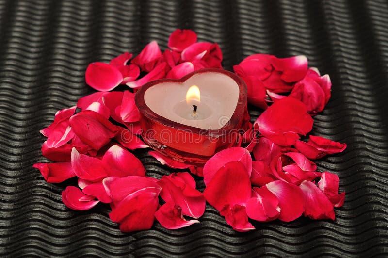 Una candela di forma del cuore con i petali rosa fotografia stock