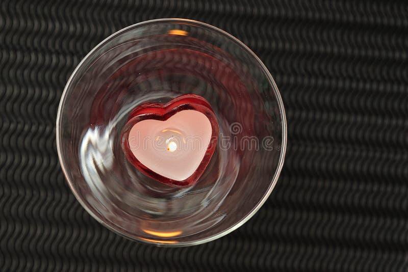 Una candela di forma del cuore visualizzata in un vetro immagini stock
