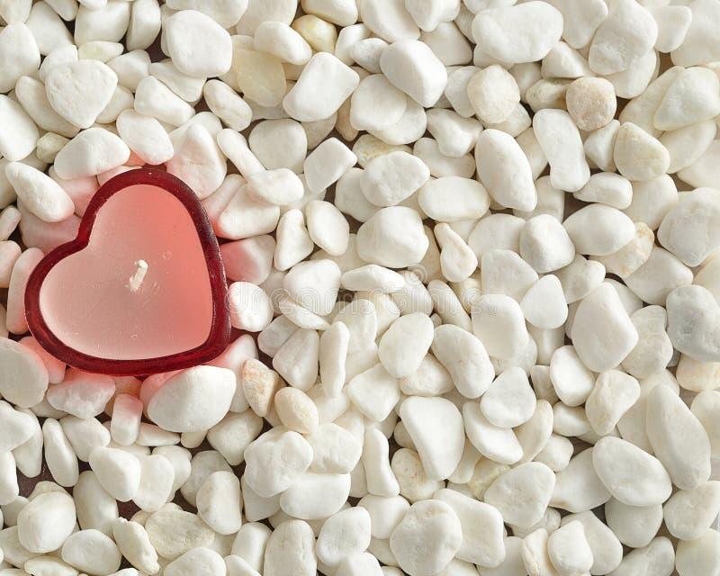 Una candela rossa di forma del cuore visualizzata sui ciottoli bianchi fotografie stock libere da diritti