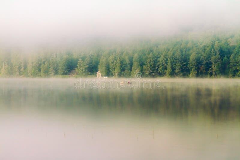 Una canoa si muove attraverso il lago nebbioso di mattina fotografie stock