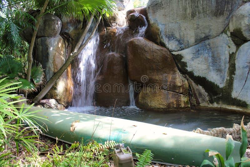 Una canoa verde embotada a lo largo del lado a la caída del agua imagen de archivo