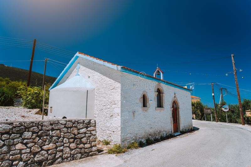 Una capilla ortodoxa griega de la pequeña tiza blanca en campo en la carretera con curvas estrecha imagen de archivo libre de regalías
