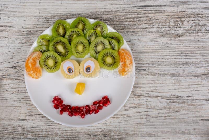 Una cara hecha de frutas en la placa imagen de archivo libre de regalías