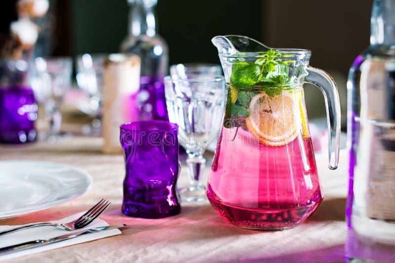 Una caraffa della bevanda fruttata con la menta ed il limone su un da portare in tavola decorato per la cena Tavola meravigliosam immagine stock libera da diritti