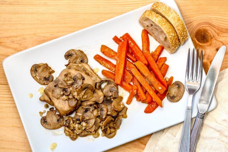 Una carne di pollo, le carote affettate, i funghi e un pane fotografie stock libere da diritti