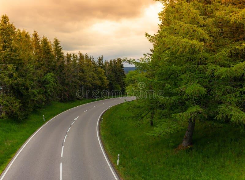 Una carretera con curvas vacía en la puesta del sol en el bosque negro en Alemania imagen de archivo libre de regalías