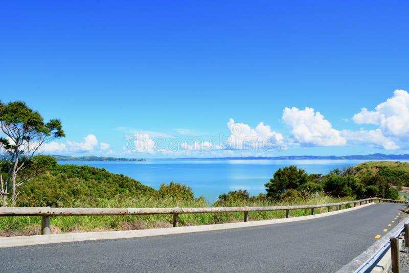Una carretera de asfalto estrecha que lleva al mar; mar azul brillante visto en una cierta distancia fotos de archivo libres de regalías
