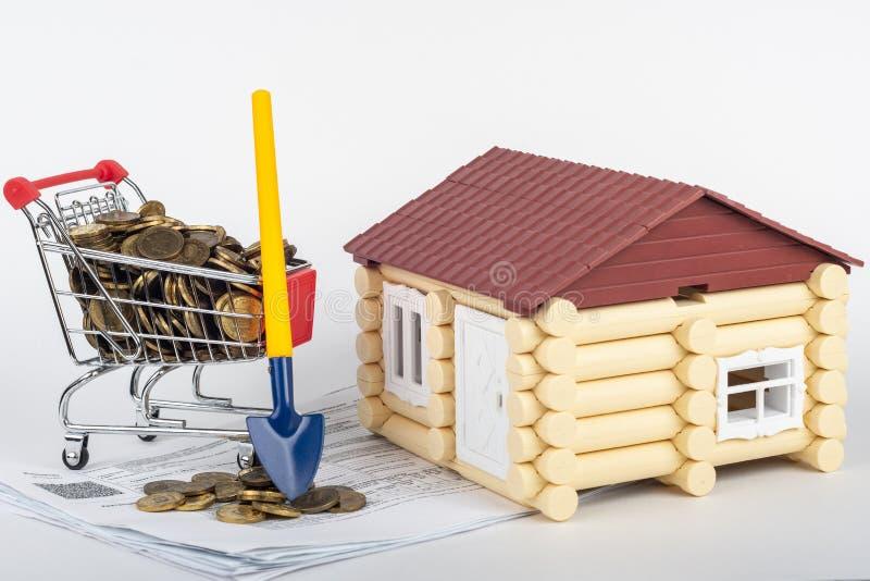 Una carretilla con el dinero en las cuentas para un apartamento, una pala se coloca al lado de ella, una casa del juguete está ce foto de archivo
