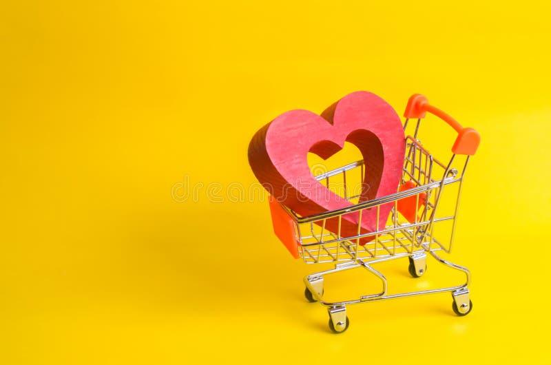 Una carretilla del supermercado con un corazón rojo dentro Amor de las compras y de las compras Tienda o supermercado preferida C fotos de archivo