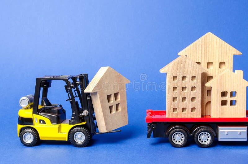 Una carretilla elevadora amarilla carga una figura de madera de una casa en un camión Concepto de envío del transporte y de cargo imagen de archivo