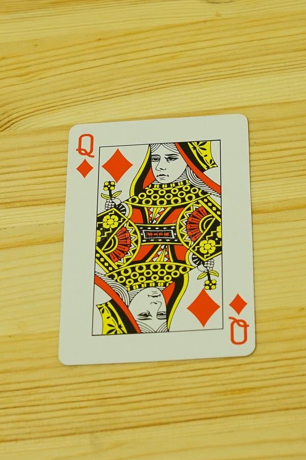 Una carta da gioco su uno scrittorio di legno immagini stock
