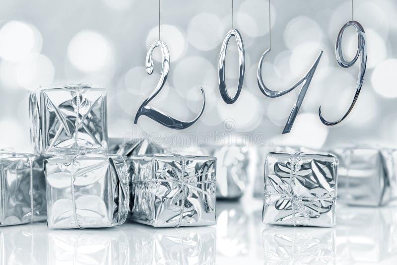 una carta da 2019 nuovi anni, piccoli regali di Natale nel fondo brillante delle luci del bokeh della carta d'argento fotografia stock