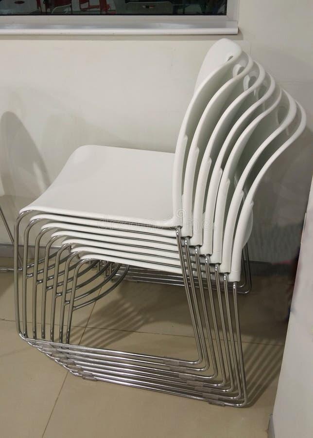 Una cartella delle sedie bianche fotografia stock