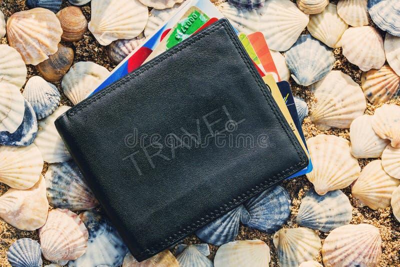 Una cartera de cuero con el VIAJE de la inscripción con las tarjetas de crédito y las tarjetas de la lealtad contra la perspectiv imagenes de archivo