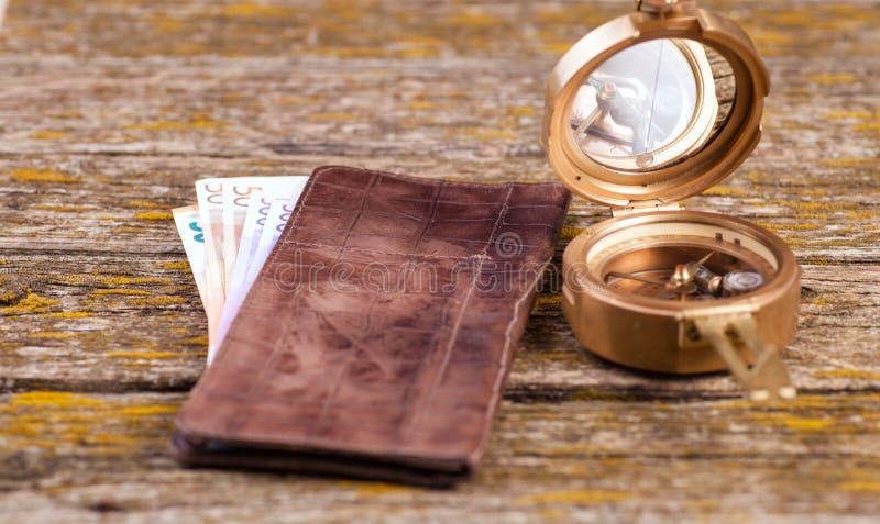 Una cartera, el dinero y otros artículos están en la tabla de viejos tableros fotografía de archivo libre de regalías