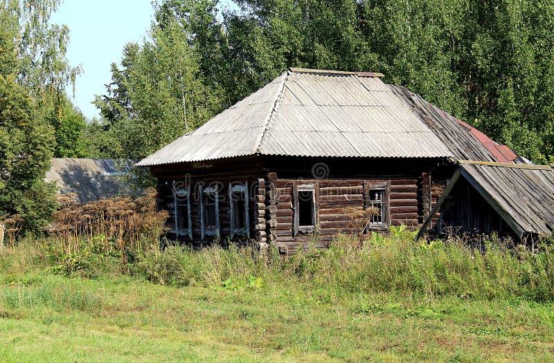 Una casa abandonada sin las ventanas se está colocando entre la hierba alta imagen de archivo