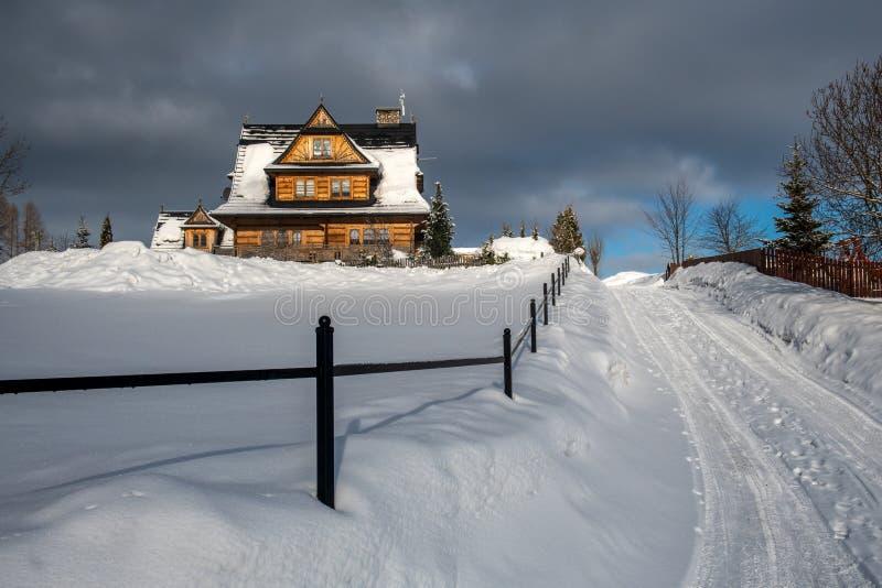 Una casa al borde del pueblo momentos antes de la tormenta de la nieve foto de archivo