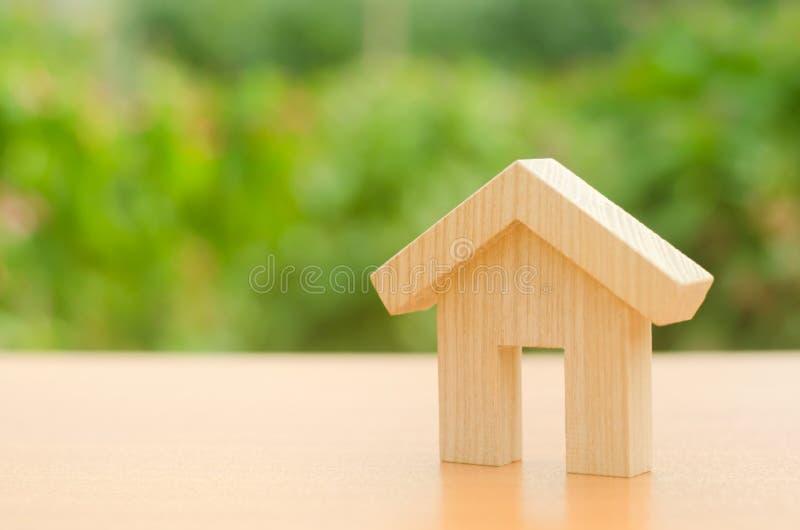 Una casa de madera se coloca en un fondo del verde de la naturaleza El concepto de comprar y de vender las propiedades inmobiliar imagen de archivo
