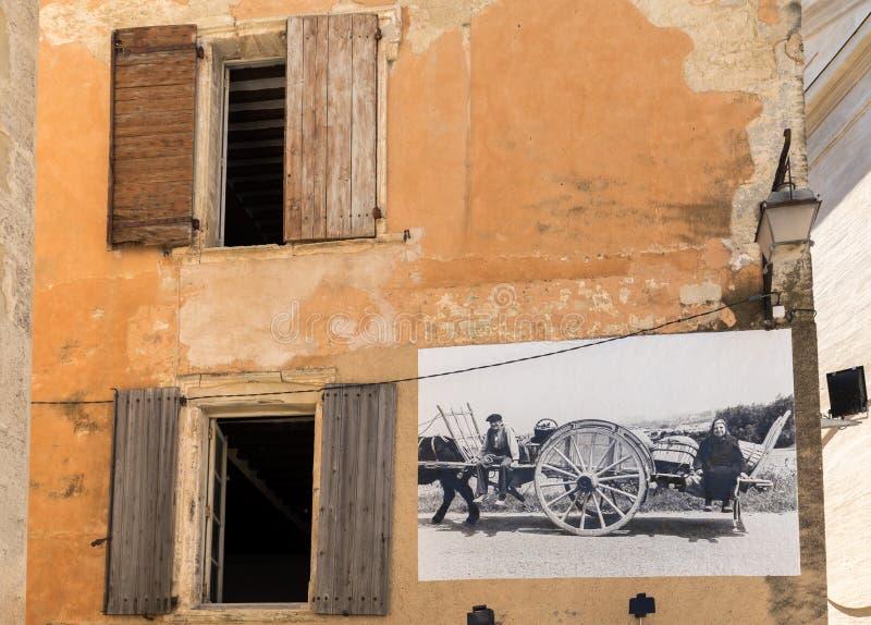 Una casa de piedra vieja típica con una cartelera que representa las escenas de la vida pasada de moda en el pueblo de Gordes, Va foto de archivo