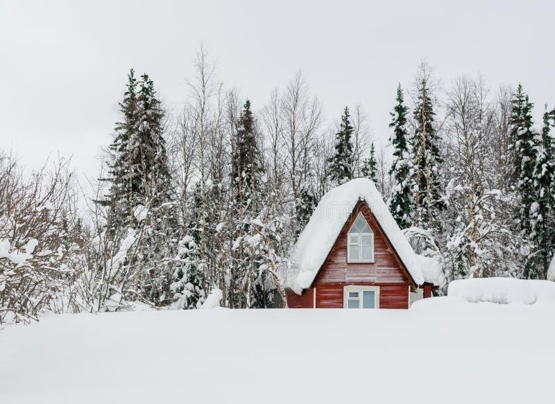 Una casa di legno in una foresta nevosa fotografia stock libera da diritti