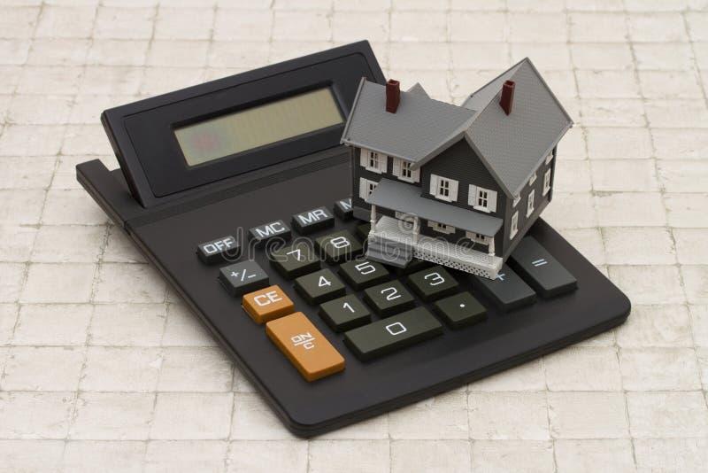 Una casa y una calculadora grises en el fondo de piedra imagenes de archivo
