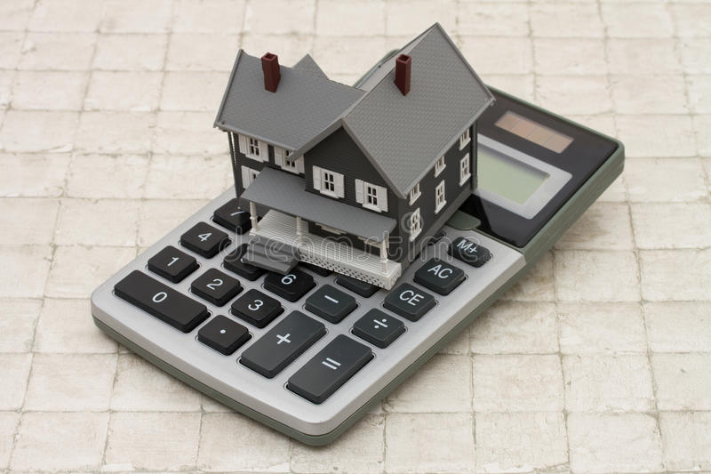 Una casa y una calculadora grises en el fondo de piedra fotos de archivo