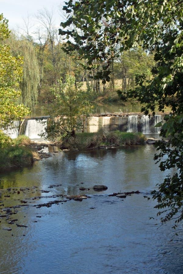 Una cascada calmante rodeada por los árboles imágenes de archivo libres de regalías