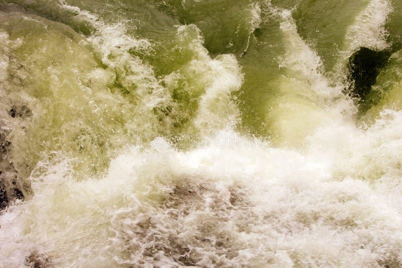 Una cascada del agua en las montañas rocosas foto de archivo libre de regalías