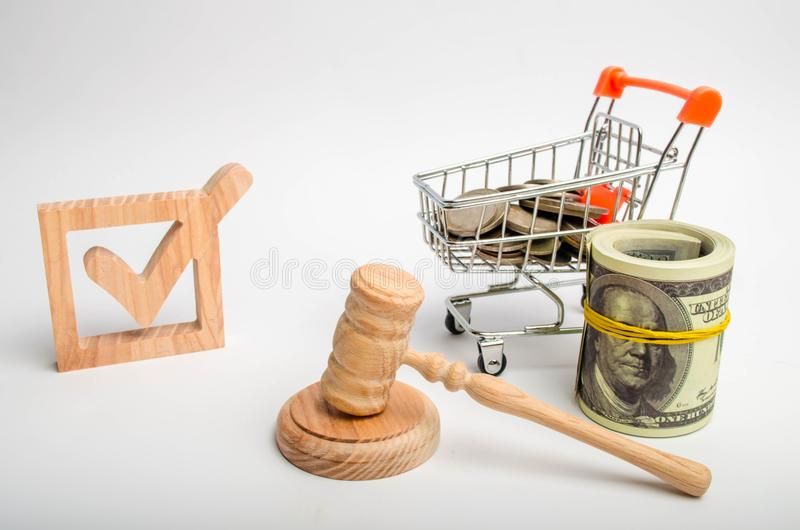 Una casella di controllo di legno e un carrello con le monete e un martello del giudice Incitamento degli interessi degli investi fotografie stock