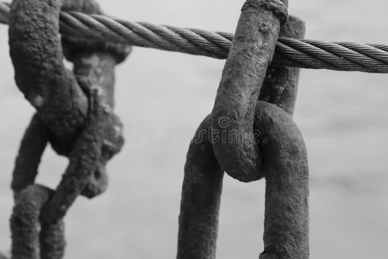 Una catena della ruggine è tenuta su un cavo in bianco e nero del metallo fotografia stock