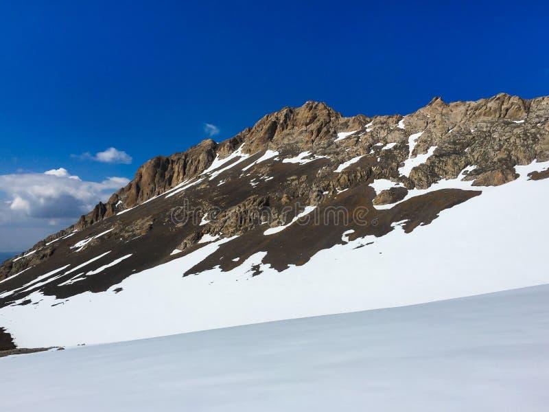 Una catena montuosa pietrosa che aumenta sopra la pianura nevosa immagini stock