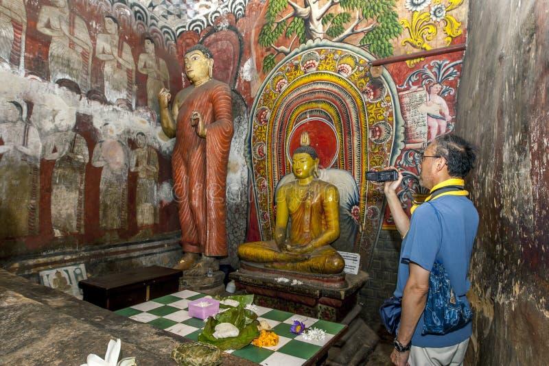 Una caverna una (Devaraja Viharaya) dell'interno dei film dell'uomo alle tempie della caverna di Dambulla nello Sri Lanka fotografia stock libera da diritti