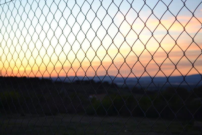 Una cerca que muestra una puesta del sol imagen de archivo