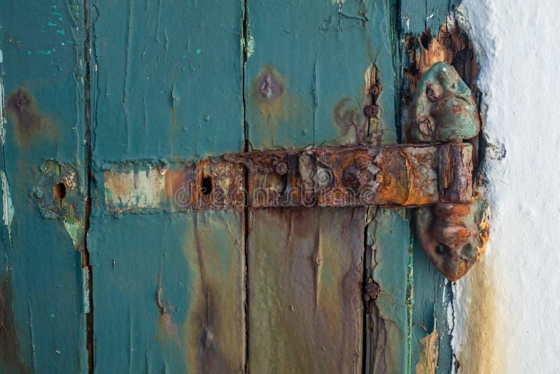 Una cerniera di porta d'arrugginimento rotta su una porta di legno dipinta, pittura che pela il legno fotografia stock libera da diritti