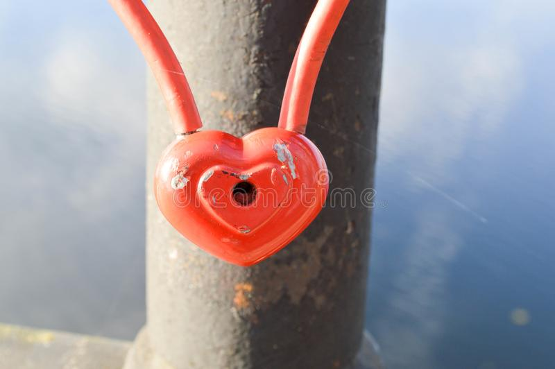 Una cerradura roja del granero en la forma de un corazón cuelga en la verja de un puente Tradición de la boda para colgar las cer imagen de archivo libre de regalías