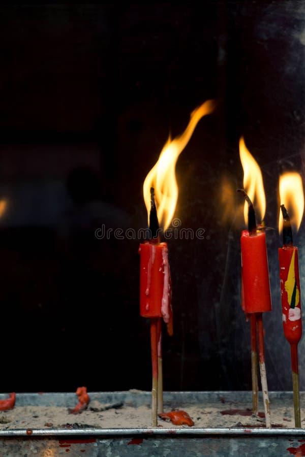 Una certa candela rossa accesa sulla sabbia immagine stock