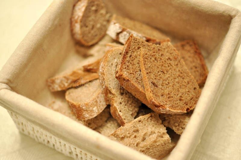 Una cesta beige de la materia textil por completo de pan marrón sano de los cereales fotos de archivo libres de regalías