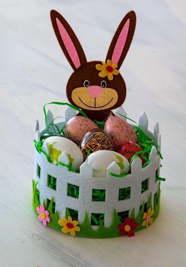 Una cesta cariñosamente adornada de Pascua con un conejito de pascua y huevos de Pascua coloridos fotografía de archivo libre de regalías