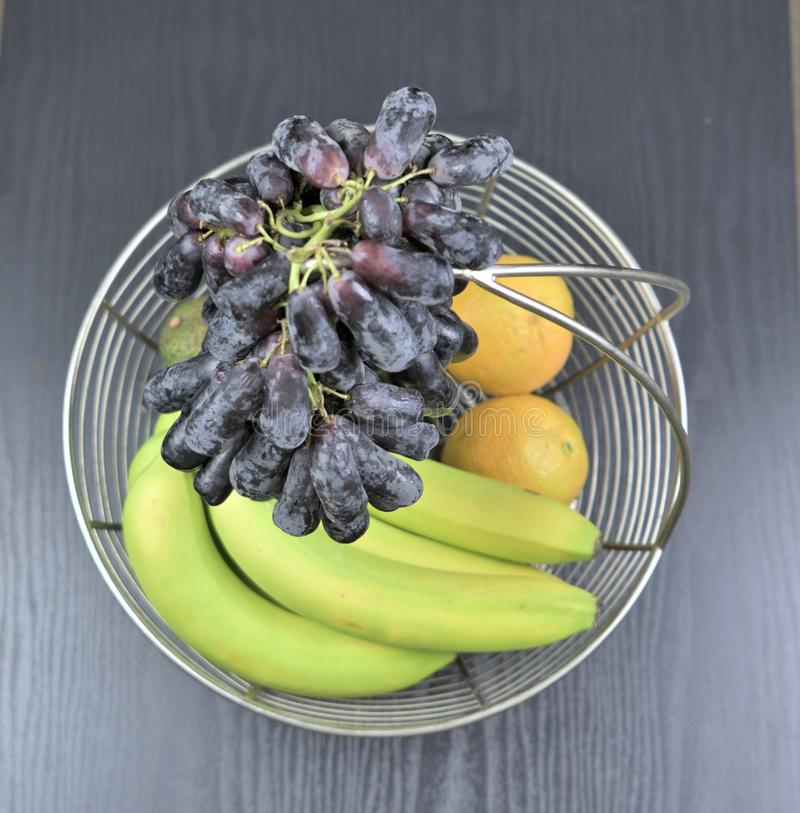 Una cesta de fruta con las uvas en el top imagen de archivo