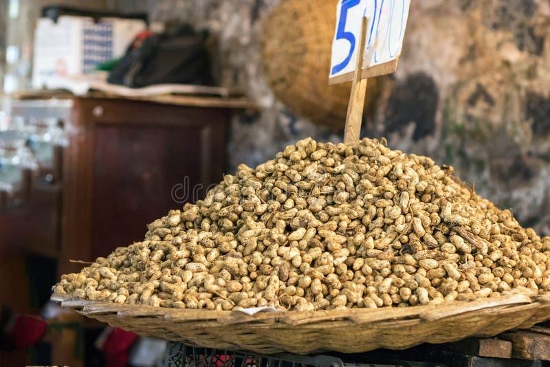 Una cesta de la paja por completo de cacahuetes en venta con el precio del tablero en el top en el mercado de Port Louis en Mauri fotos de archivo