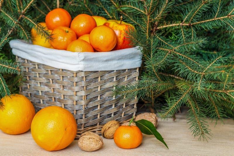 Una cesta llena de frutas maduras Mandarines, naranjas, manzanas, limones imagen de archivo