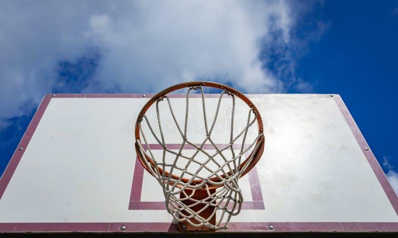 Una cesta vieja para jugar a baloncesto en el fondo de un cielo nublado brillante diurno de debajo imagen de archivo libre de regalías