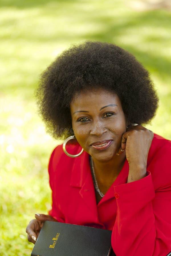 Una chaqueta más vieja del rojo de la mujer negra del retrato al aire libre fotos de archivo