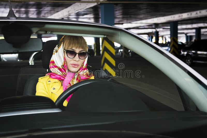 Una chica chofer de moda mira la cámara una mujer rubia glamorosa y brutal sentada en un coche cabriolet, glamurosa chica dentro  imágenes de archivo libres de regalías