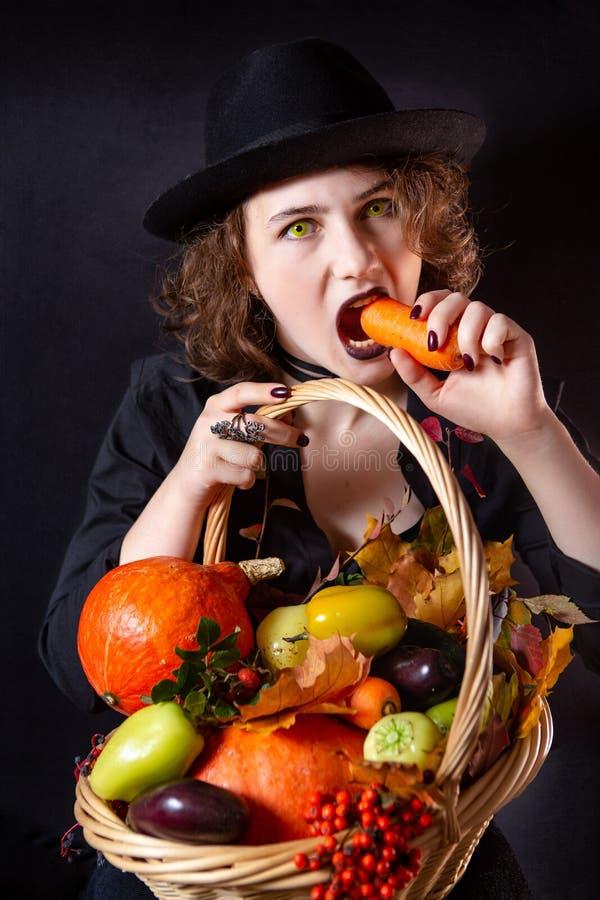 Una chica disfrazada de vampiro con ojos amarillos sostiene una canasta con verduras. Emoci?n brillante. Foto conceptual fotos de archivo libres de regalías