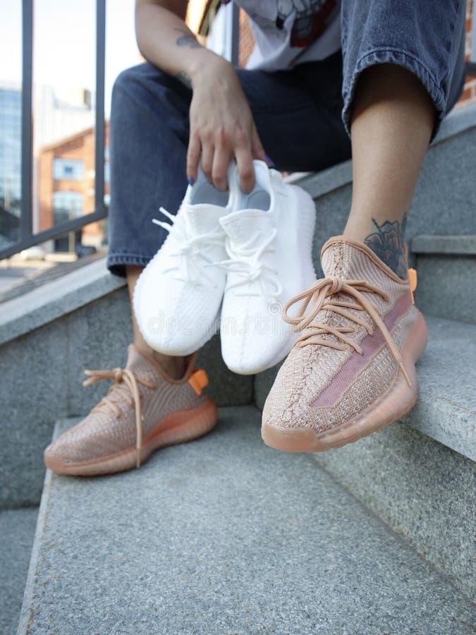 Una chica en jeans y crema Adidas Yeezy impulsa 350 V2 `lundmark´ imagenes de archivo