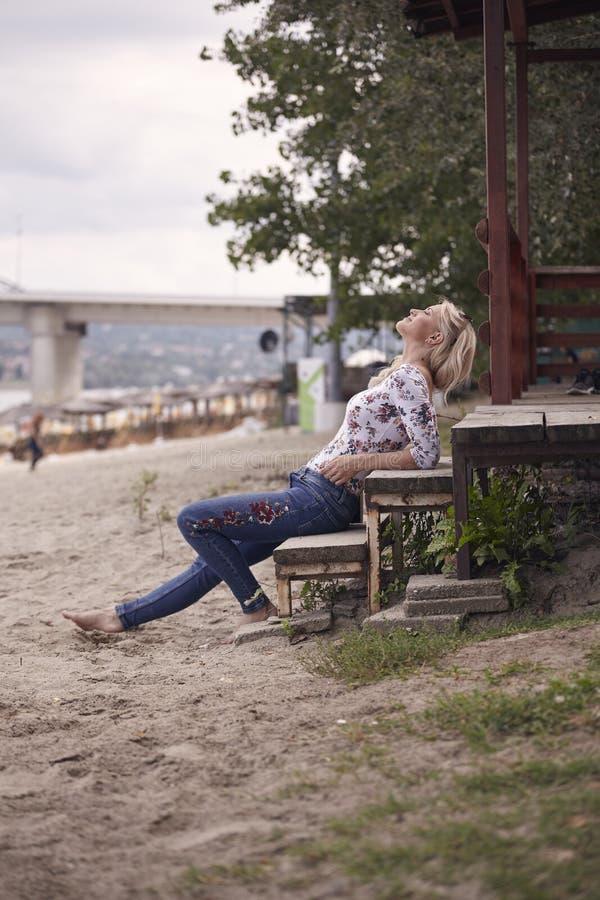 una chica joven, 25 años, sentándose en pasos en la arena de la playa, verano, sonrisa feliz, mirando para arriba arriba, al aire foto de archivo