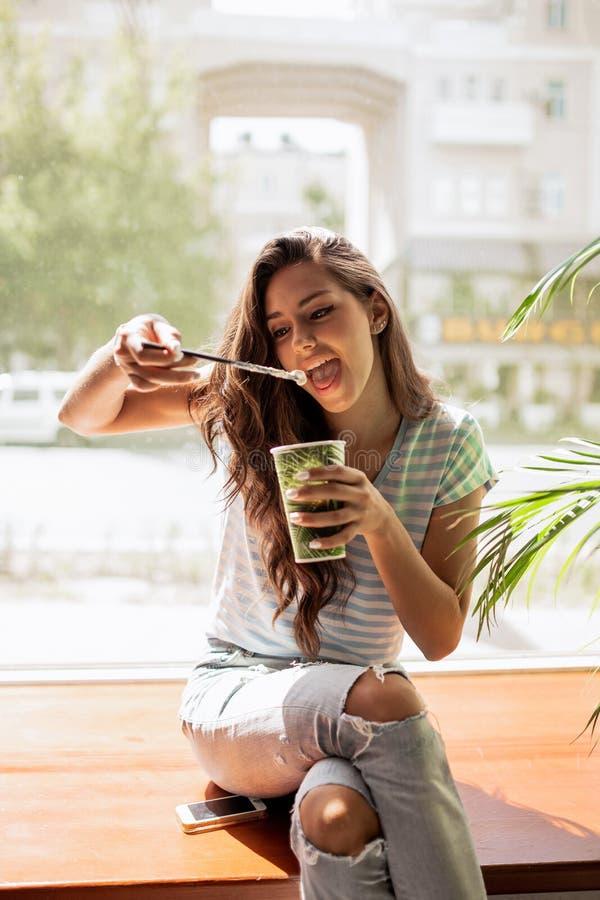 Una chica joven bastante delgada con el pelo largo, equipo casual que lleva, se sienta en el alféizar y bebe el café en un café a imagenes de archivo