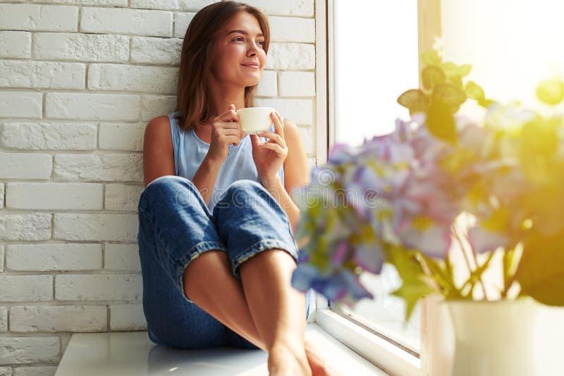 Una chica joven bien-contenta que disfruta de un día ideal que se sienta en el w foto de archivo